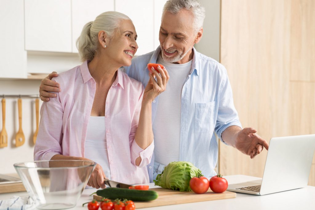 elderly couple cooking healthy foods